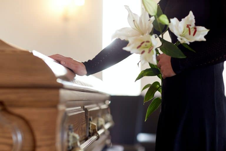 woman with flowers and coffin at funeral